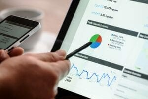 Hand pointing with stylus at monitor with several graphs | Industrial SEO services